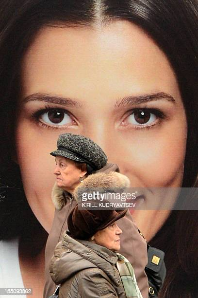 Elderly women walk past a huge advertisement showing the face of a young woman in Moscow on November 1 2012 AFP PHOTO / KIRILL KUDRYAVTSEV