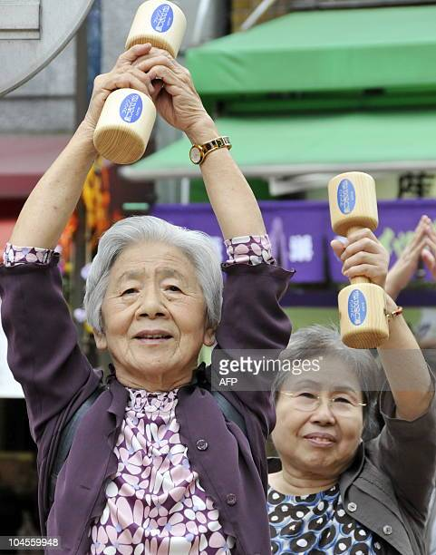 Elderly women work out with wooden dumbbells in the grounds of a temple in Tokyo on September 21 2009 to celebrate Japan's RespectfortheAgedDay The...