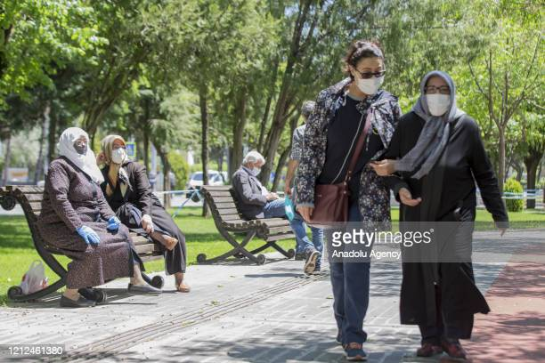 Elders enjoy sun after people over 65-year-old are allowed to leave their homes, remaining within walking distance and wearing masks, between 11 a.m....