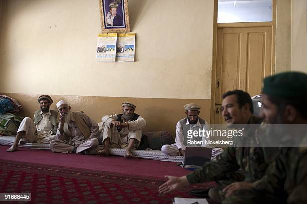 Elders from the Shuryak Valley listen to the local Afghan National Army commander speak with US Army officers from the 4th Infantry Division's 4th...