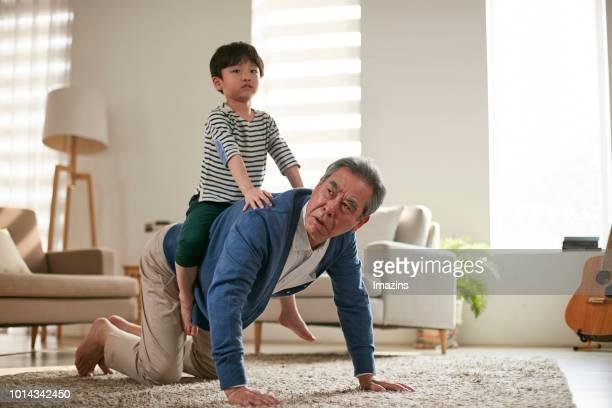 elders taking care of grandchildren - portare a cavalluccio foto e immagini stock