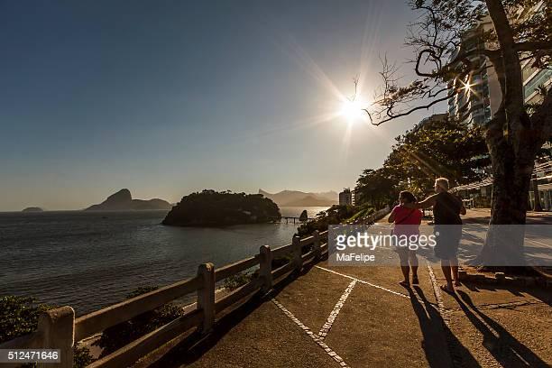 Idosos Casal a passear por litoral ao pôr do sol