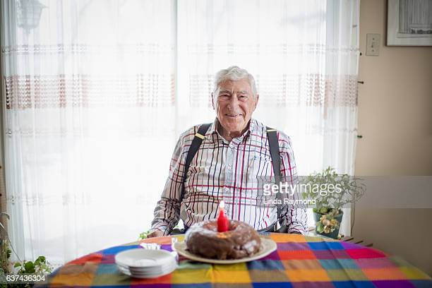 Eldery smiling  in front of his birthday cake