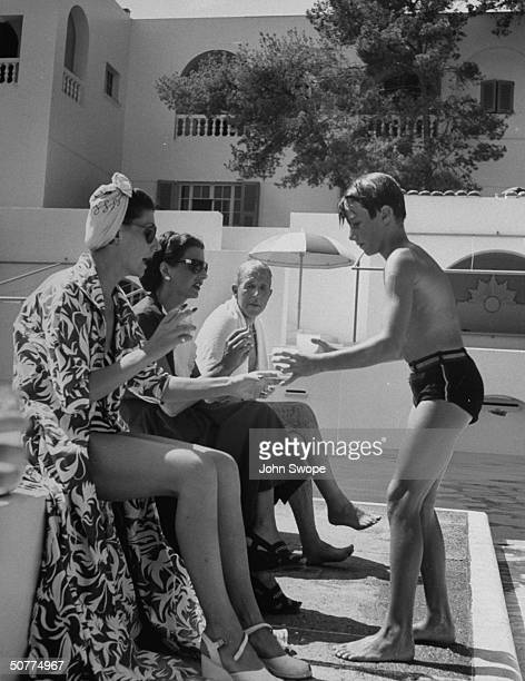Eldest son of Prince Aly Khan Karim AGA Khan IV serving drinks to Mrs FH Hanbury Mrs GA Roelandts and Lord Willoghby de Brooke