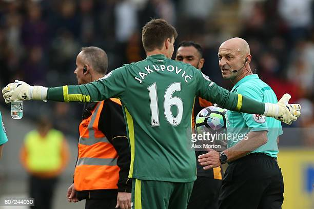 Eldin Jakupovic of Hull City argues with referee Roger East during the Premier League match between Hull City and Arsenal at KCOM Stadium on...