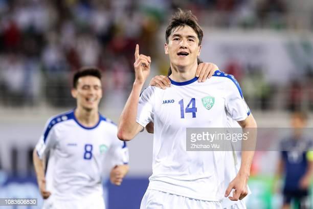 Eldor Shomurodov of Uzbekistan celebrates his scoring with teammates during the AFC Asian Cup Group F match between Japan and Uzbekistsn at Khalifa...
