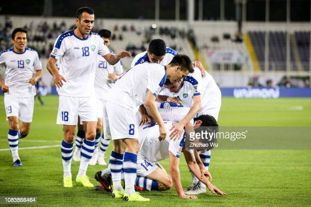 Eldor Shomurodov of Uzbekistan celebrates his scoring with teammates during the AFC Asian Cup Group F match between Japan and Uzbekistsn at Khalifa...