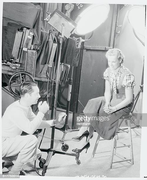 Eleanor Holm, Olympic swimming champion, is right in the movie swim now. Here she is being photographed by Elmer Fryer, head still photographer at...