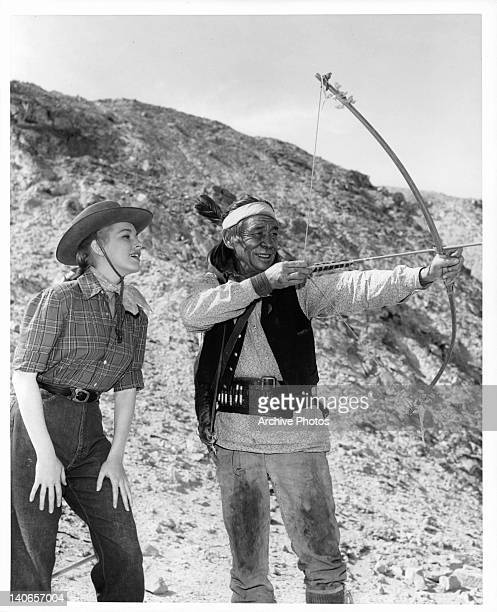 Eleanor Parker is shown how to shoot a bow by Charles Stevens in a scene from the film 'Escape From Fort Bravo' 1953
