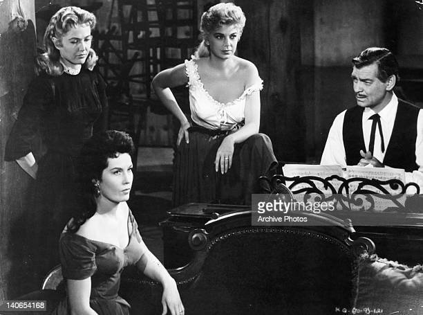 Eleanor Parker Jean Willes and Barbara Nichols gathered near Clark Gable at the piano in a scene from the film 'The King And Four Queens' 1956