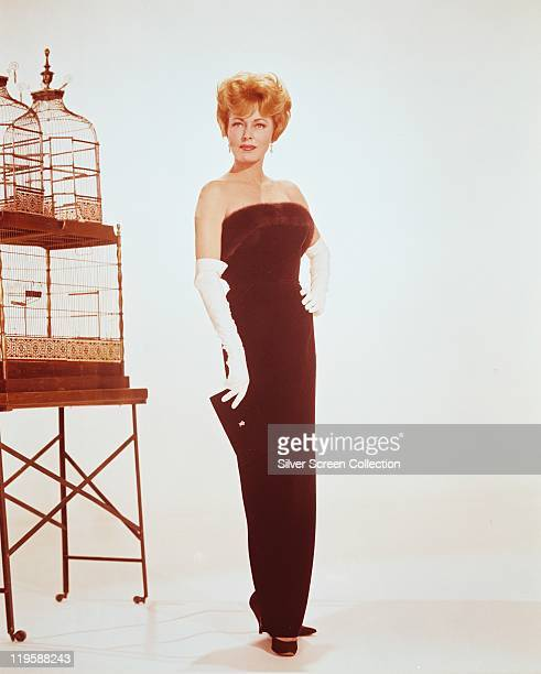 Eleanor Parker US actress wearing a long deep red strapless dress and long white gloves while posing beside a birdcage in a studio portrait against a...