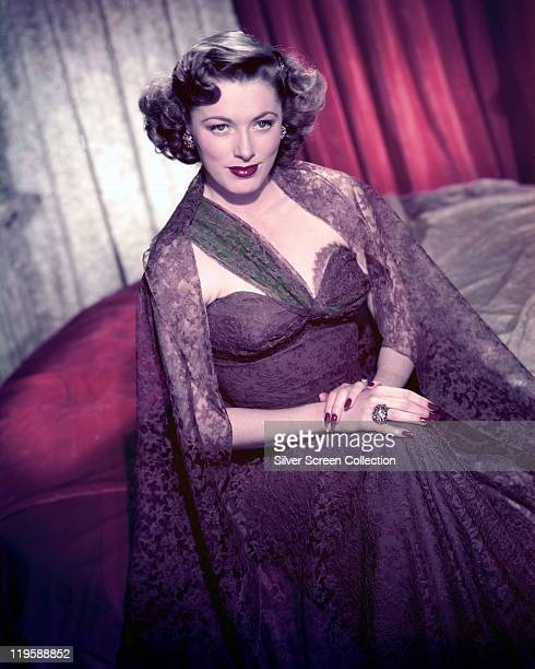 Eleanor Parker US actress wearing a low cut strapless purple dress and a purple lace shawl in a studio portrait circa 1955