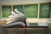 E-learning online education or internet  encyclopedia concept. Open laptop and book compilation in a classroom.