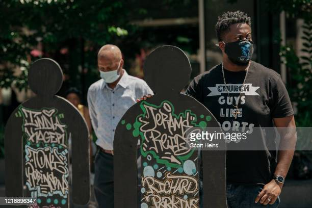 Elected officials and local clergy leaders hold up statues bearing the names of people killed by police on June 9, 2020 in the Bedford Stuyvesant...