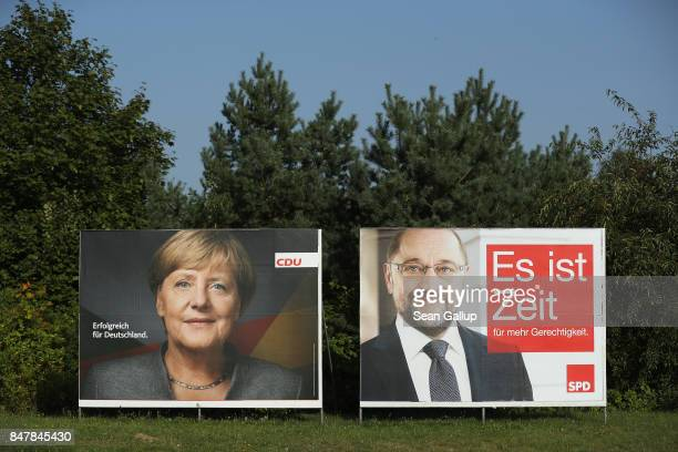 Election campaign billboards that show German Chancellor and Christian Democrat Angela Merkel and German Social Democrat chancellor candidate Martin...