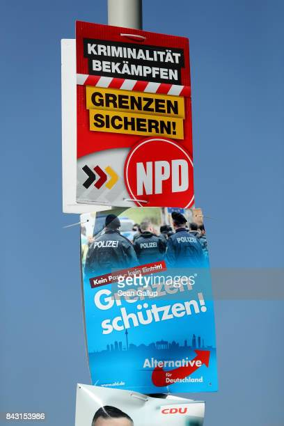 Election campaign posters of the farright NPD which reads Secure Borders and of the rightwing populist Alternative for Germany which reads Protect...