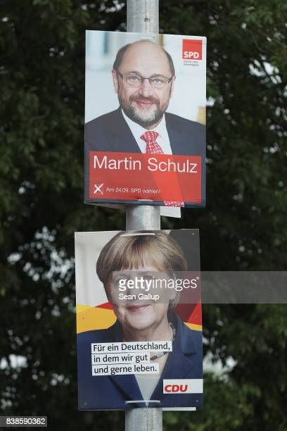Election campaign posters that depict German Social Democrat and chancellor candidate Martin Schulz and German Chancellor and Christian Democrat...