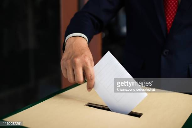 election concept. hand dropping a ballot card into the vote box,drop the ballot - referendum stock pictures, royalty-free photos & images