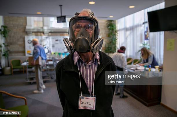 Election inspector David Hopkinson wears a full-face ventilator as a protection against Covid-19 while working at the Emanuel First Lutheran School...