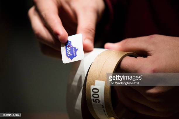 RICHMOND KENTUCKY USA NOVEMBER 6 2018 Election Judge Hunter Winkler hands out Kentucky themed I Voted stickers to voters at the Eastern Kentucky...