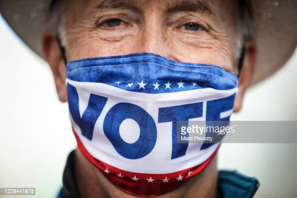 Election judge Michael Firth of Denver, Colorado waits for voters to drop off ballots at a drive-thru ballot drop location outside the Denver...