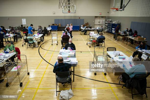 Election judges wearing protective masks prepare mail-in ballots to be scanned by the Montgomery County Board of Elections at a recreation center in...