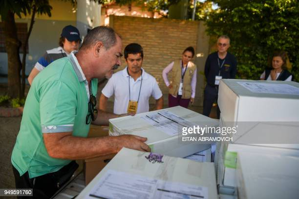 Election observers from the European Union and the Organization of American States look at workers downloading voting material at a polling station...