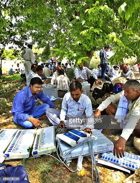 Election officers checking their Electronic Voting Machines at a distribution centre on May 11 2014 in Varanasi India Varanasi a highprofile...