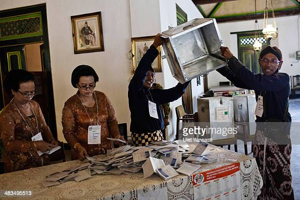 Election officers in traditional javanese costume show empty ballot box as they prepare paper ballots for vote count at a polling station after the...