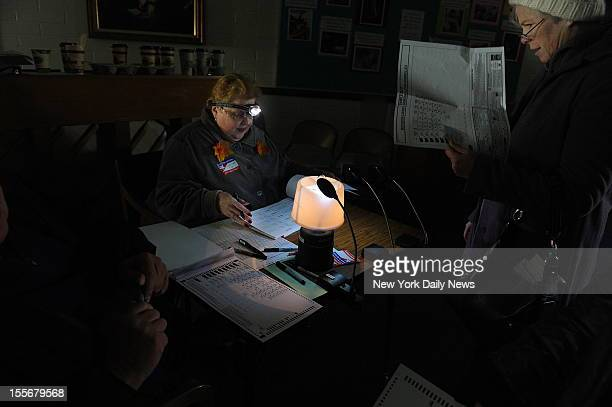 Election Official Christina Fox uses a headlamp to illuminate emergency ballots and check voters in while shivering in the dark. Voters were handed...
