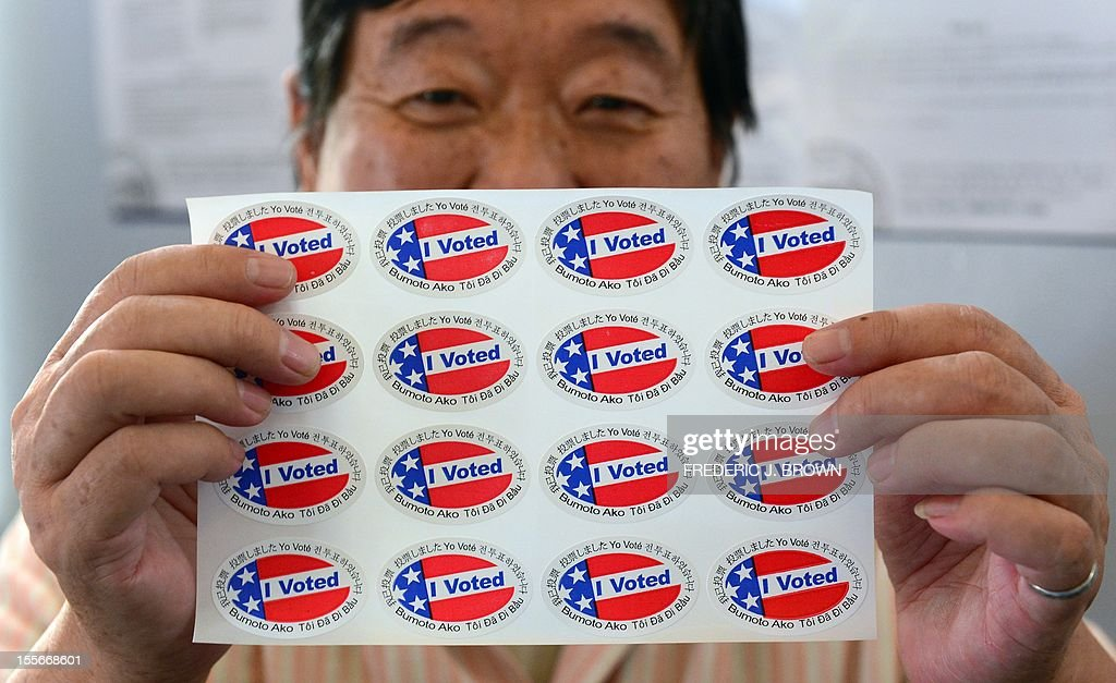 Election official Henry Tung displays a sheet of 'I Voted' stickers in various languages at a polling station at St. Paul's Lutheran Church in Monterey Park, Los Angeles County, on November 6, 2012 in California, as Americans flock to the polls nationwide to decide between President Barack Obama, his Rebuplican challenger Mitt Romney, and a wide range of other issues. Monterey Park is one of six cities in California's 49th Assembly District, the state's first legislative district where Asian-Americans make up the majority of the population. AFP PHOTO/Frederic J. BROWN