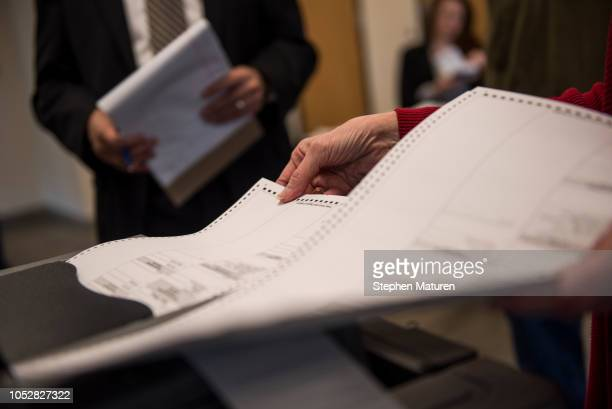 Election official Mary Wickersham feeds a test ballot into a vote counting machine during a public accuracy test of Election Day voting machines at...
