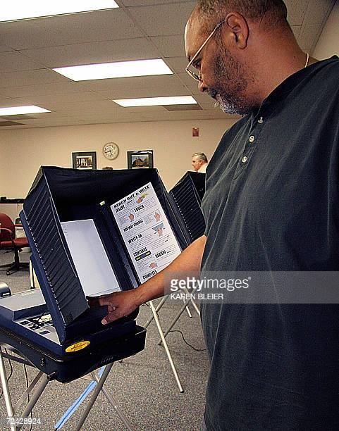 Election official Ralph Wheeler sets up an electronic voting machine 07 November 2006 before the opening to voters at the Sudley North Government...