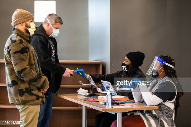 Election officials assist voters at a polling location during the Senate runoff elections in Atlanta, Georgia, U.S., on Tuesday, Jan. 5, 2021....