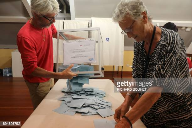 Election officials empty a ballot box to start counting votes at a polling station in SaintLeu on the French overseas island of La Reunion on June 11...