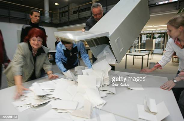 Election officials empty a ballot urn to begin counting ballots at a polling station in voting district 160 October 2 2005 in Dresden Germany Due to...