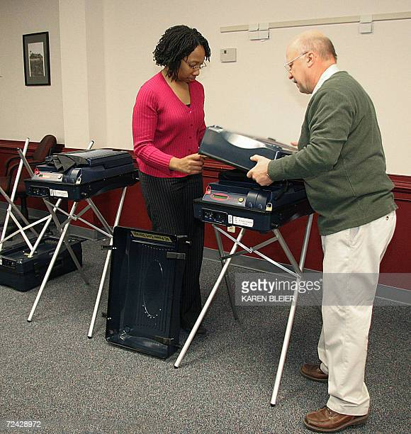 Election officials John Masarick and Crystal Lamb set up electronic voting machines 07 November 2006 prior to the opening of the polls at the Sudley...