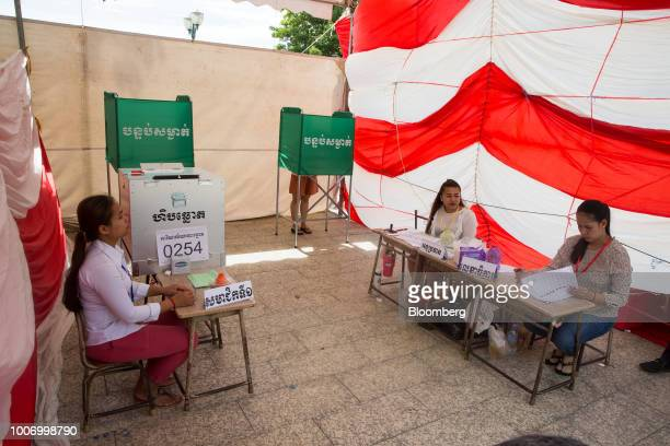 Election officials sit at their desks at a polling station in Phnom Penh Cambodia on Sunday July 29 2018 As Cambodians vote on Sunday a win is all...