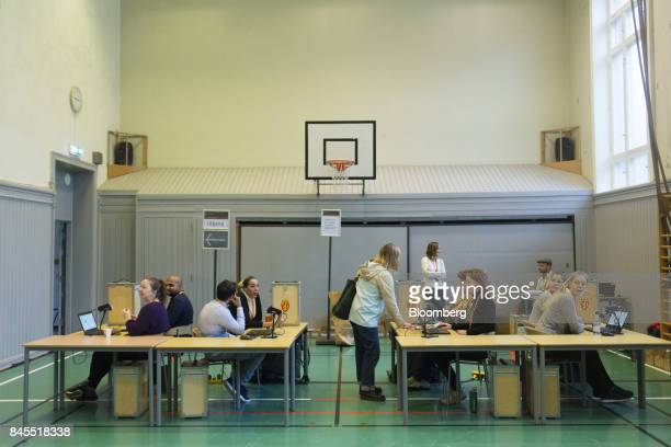 Election officials wait for voters beside ballot boxes at a school polling station on the final day of the parliamentary vote in Oslo Norway on...