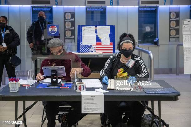 Election officials wearing protective masks work at a polling location for the 2020 Presidential election at Madison Square Garden in New York, U.S.,...