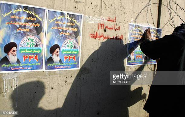 Election posters are plastered on large cement blocks protecting the entrance to a police station 21 January 2005 in the northeastern city of Baquba...