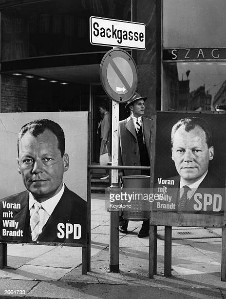 Election posters for the Social Democratic Union party proclaiming 'Ahead with Willy Brandt' placed next to a road sign pointing 'Into a blind alley'.