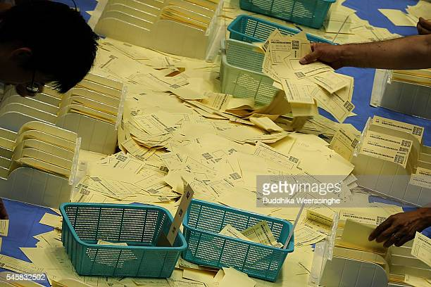 Election staff members count votes which were cast in the Parliament's upper house election at a ballot counting center on July 10 2016 in Himeji...