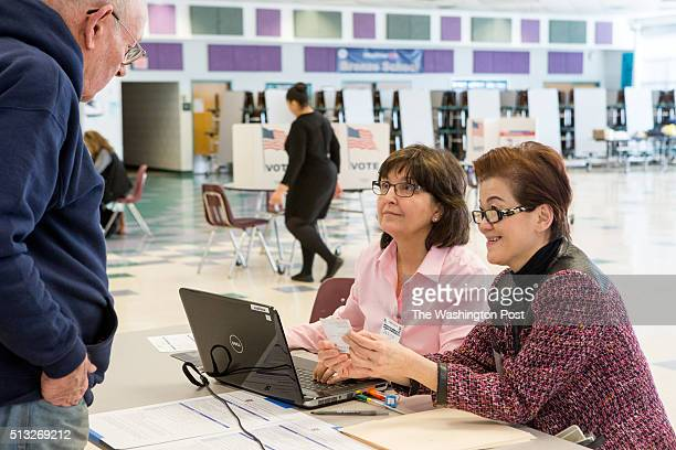 Election volunteers Janice Wolfe left and Ly Hom right check in voters so they can cast their ballots in the presidential primary at Rachel Carson...
