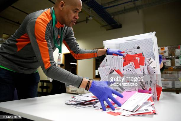 Election worker Erick Moss sorts vote-by-mail ballots for the presidential primary at King County Elections in Renton, Washington on March 10, 2020.