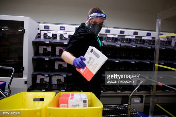 Election worker Gareth Fairchok removes ballots from a sorting machine as vote-by-mail ballots for the August 4 Washington state primary are...