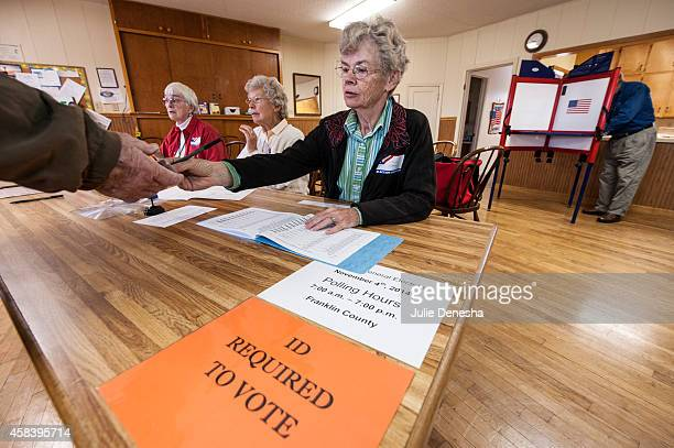 Election worker Karen Witham checks voter identifications in the Richter Church November 4 2014 in Centropolis Township near Ottawa Kansas A tight...