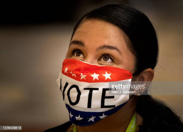 Election worker Melissa Balderas wears a vote mask while assisting early voters in the General Election at the Honda Center on Monday, Nov. 2, 2020...