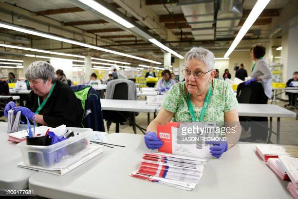 Election worker Ruth Ard opens votebymail ballots for the presidential primary at King County Elections in Renton Washington on March 10 2020