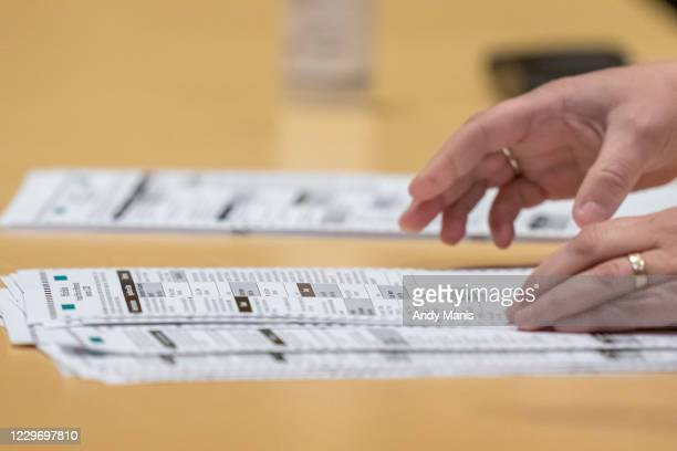 Election worker shows ballots to representatives for President Donald Trump during the presidential recount vote for Dane County on November 20, 2020...